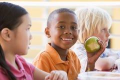 Kindergarten children eating lunch. Smiling royalty free stock photos