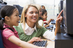 Kindergarten children learn to use computers. Teacher helping kindergarten children learn how to use computers Royalty Free Stock Photos