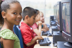 Kindergarten children learning to use computers.