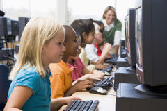 Kindergarten children learning to use computers Royalty Free Stock Image