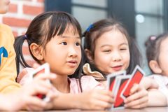 Children playing with counting card in class room. Kindergarten children playing with counting card in class room royalty free stock image