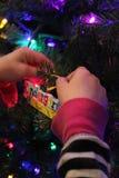 Kindergarten Christmas. Child hanging ornaments on tree stock image