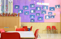 Kindergarten class with small red chairs and children's drawings Stock Photo
