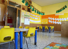 Kindergarten classroom with chairs and table with drawings of ch Royalty Free Stock Photos