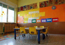 Kindergarten classroom with chairs and table with drawings Royalty Free Stock Image
