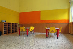 Kindergarten classroom with desks and yellow chairs Royalty Free Stock Images