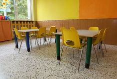 Kindergarten classroom with desks and yellow chairs without kids. Kindergarten with desks and yellow chairs royalty free stock photography