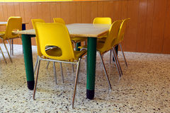 Kindergarten with desks and yellow chairs without kids. Kindergarten classroom with desks and yellow chairs stock images