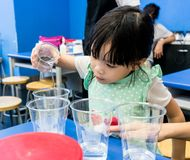 Kindergarten girl pouring clear solution into a cup on blue tabl. E. Starting a simple science experiments for young scientist learning Royalty Free Stock Photo