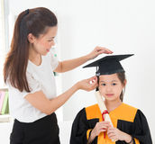 Kindergarten graduation. Asian child graduation, teacher adjusting cap for student indoor royalty free stock photo