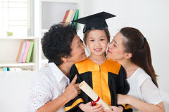 Kindergarten graduation. Asian family, grandparent and parent kissing grandchild on her kinder graduate day stock image