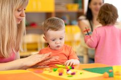 Kindergarten kid learning with teacher in nursery stock images