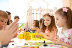 Kindergarten kids doing arts and crafts with teacher in day care centre royalty free stock photo