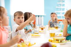 Kindergarten kids have a lunch. Children have a fun around with food stock photography