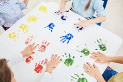 Hand prints. Kindergarten kids making colorful hand prints on paper while having fun at leisure stock photography