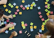 Kindergarten kids playing wooden alphabets letters vocabulary ga. Kindergarten kids playing wooden alphabets letters vocabulary Royalty Free Stock Image