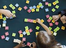 Kindergarten kids playing wooden alphabets letters vocabulary ga. Kids playing wooden alphabets letters vocabulary game Royalty Free Stock Images