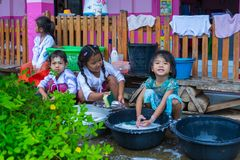 Kindergarten kids in rural nursery school washing dishes, bowls stock photos