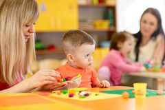 Kindergarten kids with teacher mould from plasticine on table in nursery stock photography