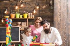 Kindergarten-Konzept Spiel des kleinen Jungen mit Spielzeugziegelsteinen im Kindergarten FamilienGebäudestrukturmodell im Kinderg lizenzfreie stockfotos