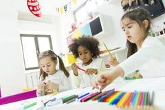 Kindergarten. Little girls drawing and learning in the kindergarten stock image