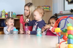 Kindergarten or nursery kidson a table drinking and playing Royalty Free Stock Images