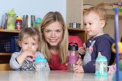 Kindergarten oder Kindertagesstätte kidson eine Tabelle, die 2 trinkt und spielt stockfotos