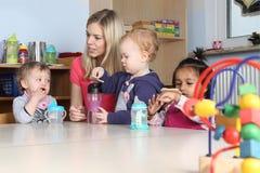 Kindergarten oder Kindertagesstätte kidson eine trinkende und spielende Tabelle lizenzfreie stockbilder