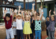 Kindergarten students with arms raised. Diverse kindergarten students with arms raised Stock Images
