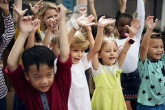 Kindergarten students with arms raised Stock Images