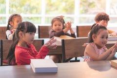 Kindergarten students dancing shark in classroom royalty free stock images