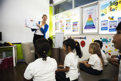 Kindergarten students sitting on the floor in the classroom Royalty Free Stock Photos