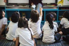 Kindergarten students sitting on the floor royalty free stock photo