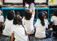 Kindergarten students sitting on the floor listening to teacher stock photo