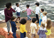 Kindergarten students standing holding hands in circle form royalty free stock photography