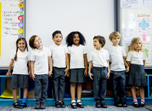 Kindergarten students standing together in clas. Group of diverse kindergarten students standing together in classroom Royalty Free Stock Image
