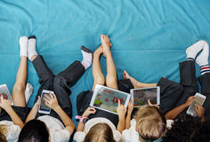 Kindergarten students using digital devices. Group of diverse kindergarten students using digital devices aerial view flat-lay Royalty Free Stock Images
