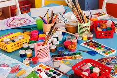 Kindergarten tables and chairs in interior decoration shelves for toys. Stock Photography