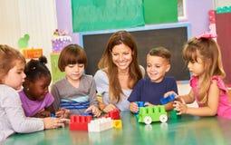 Free Kindergarten Teacher And Children Play With Building Blocks Stock Image - 219272791