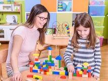 Kindergarten Teacher and Child. Kindergarten Teacher Helping Child in Creative Activities Stock Photography