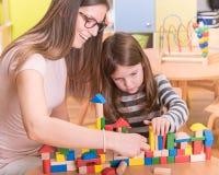Kindergarten Teacher and Cute Girl Buliding Toy Castle. Harnessing Creativity in the Kindergarten and Preschool Royalty Free Stock Photos