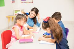 Kindergarten teacher with her students. Happy kindergarten female teacher helping her students with some writing exercise in the classroom royalty free stock photography