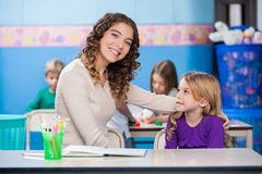 Kindergarten Teacher With Little Girl In Classroom. Portrait of beautiful kindergarten teacher with little girl sitting at desk in classroom Royalty Free Stock Photography