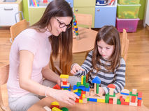 Kindergarten Teacher Playing with Child Stock Photo