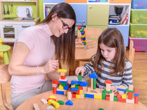 Kindergarten Teacher Playing with Child with Toy Blocks. Kindergarten Teacher Helping Child in Creative Activities Royalty Free Stock Image