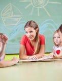 Kindergarten teacher reading book. Nursery teacher reading book for children in a kindergarten Royalty Free Stock Image