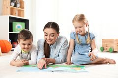 Kindergarten teacher reading book to children. Learning and playing royalty free stock photos