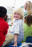 Kindergarten teacher reading to children. In library, boy looking Stock Image