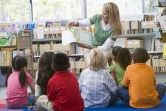 Kindergarten teacher reading to children stock photos