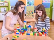 Kindergarten Teacher Supporting sad Child. Kindergarten Teacher Helping Child in Creative Activities Stock Image